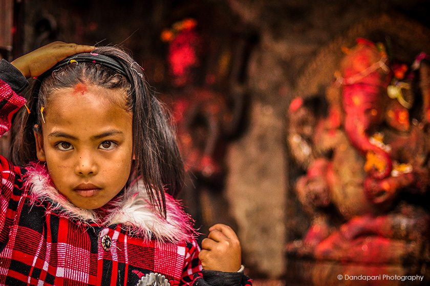 A young girl places blessed flower petals in her hair after worshipping Ganesha at a roadside shrine in Kathmandu, Nepal.
